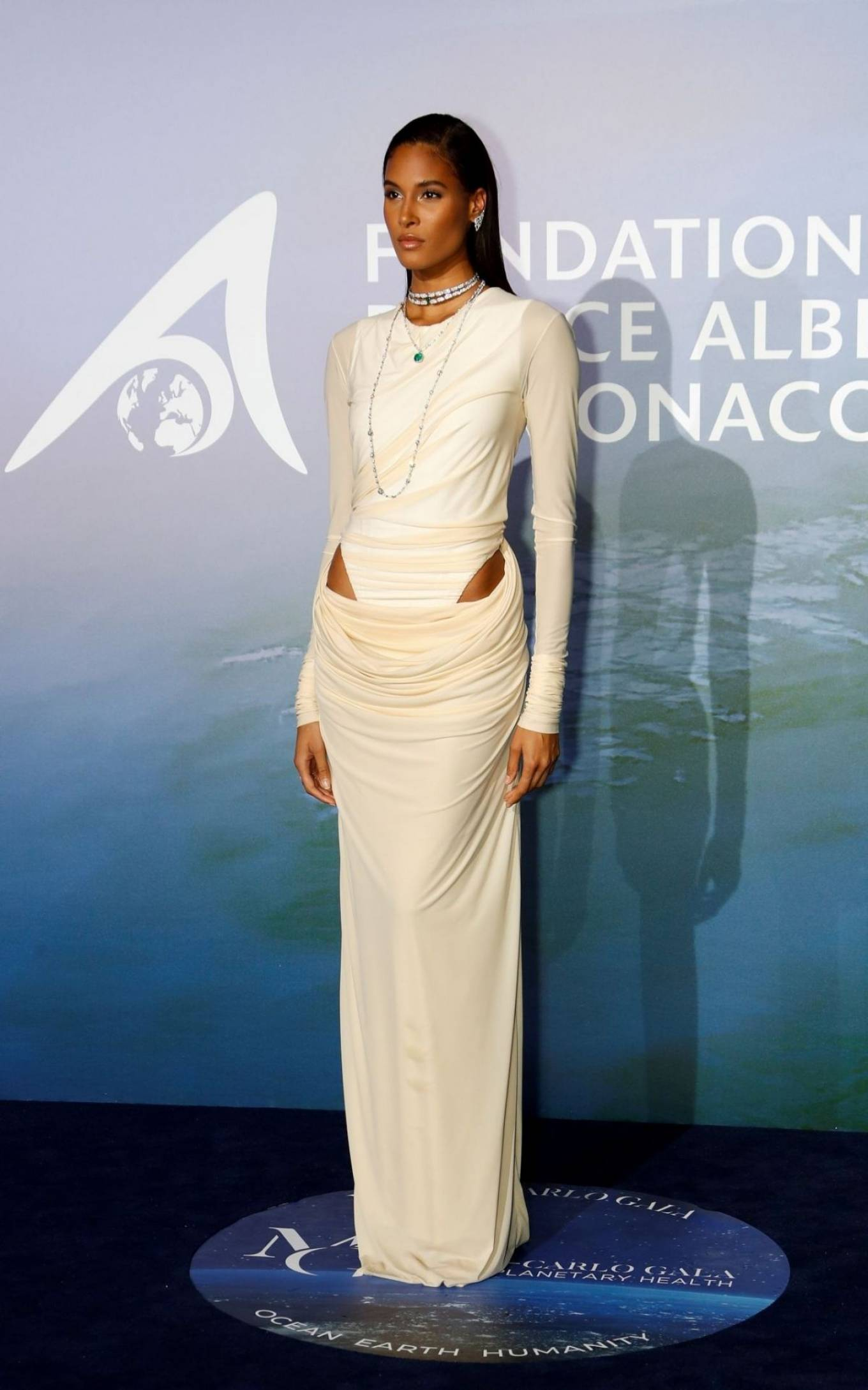 Cindy Bruna wearing a Slouchy off white draped maxi dress with full sleeves, asymmetric design, a round neck and drop waist