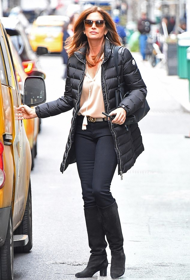 Cindy Crawford wearing narrow black suede mid calf boots with block heel