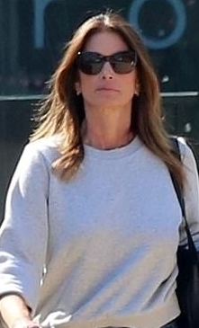 Cindy Crawford donning black mesh lace-up sneakers with contrasting sole