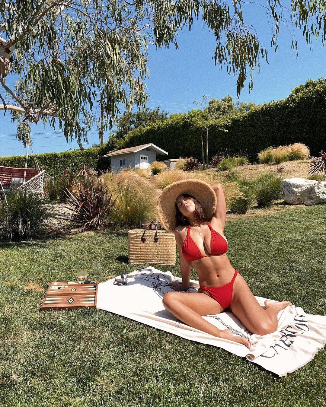 Devin Brugman donning a Plunging paprika red Monday Swimwear bikini top with ruched and spaghetti straps