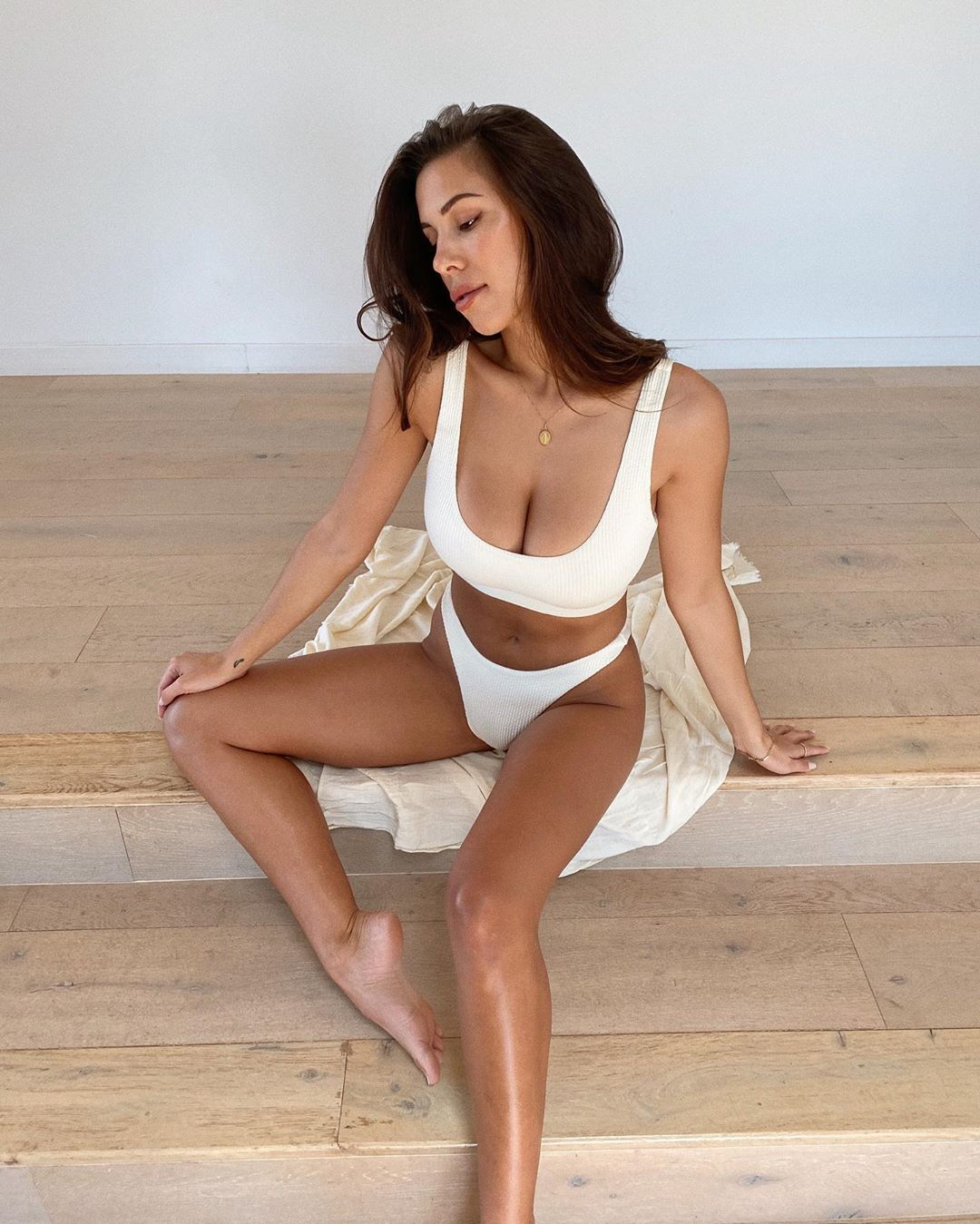 Devin Brugman wearing a White ribbed Monday Swimwear crop top with a ribbed fabric material, a scoop neck and wide strap