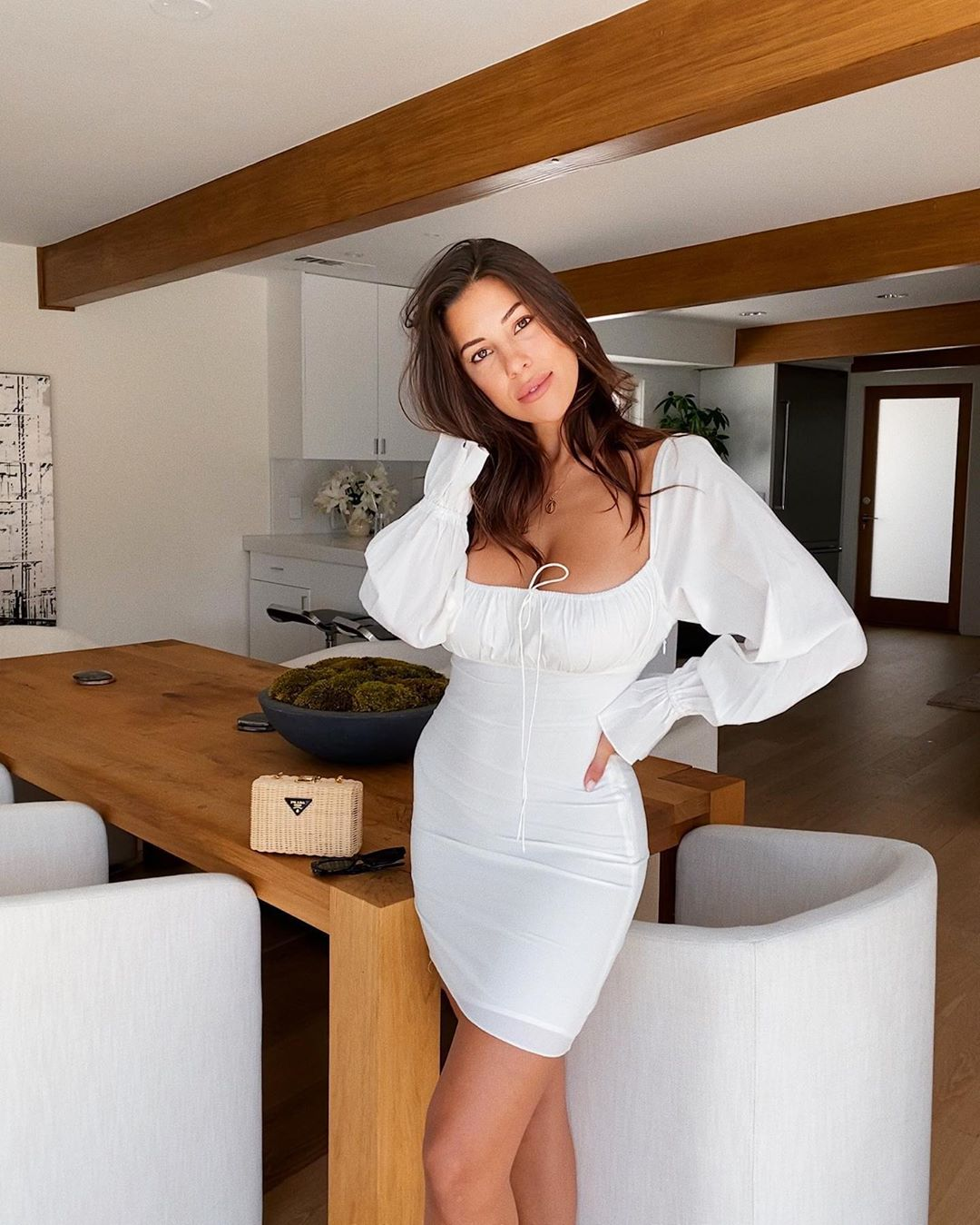 Devin Brugman wearing a Formfitting white With Jean mini dress with puffy sleeves, ruched and a scoop neck