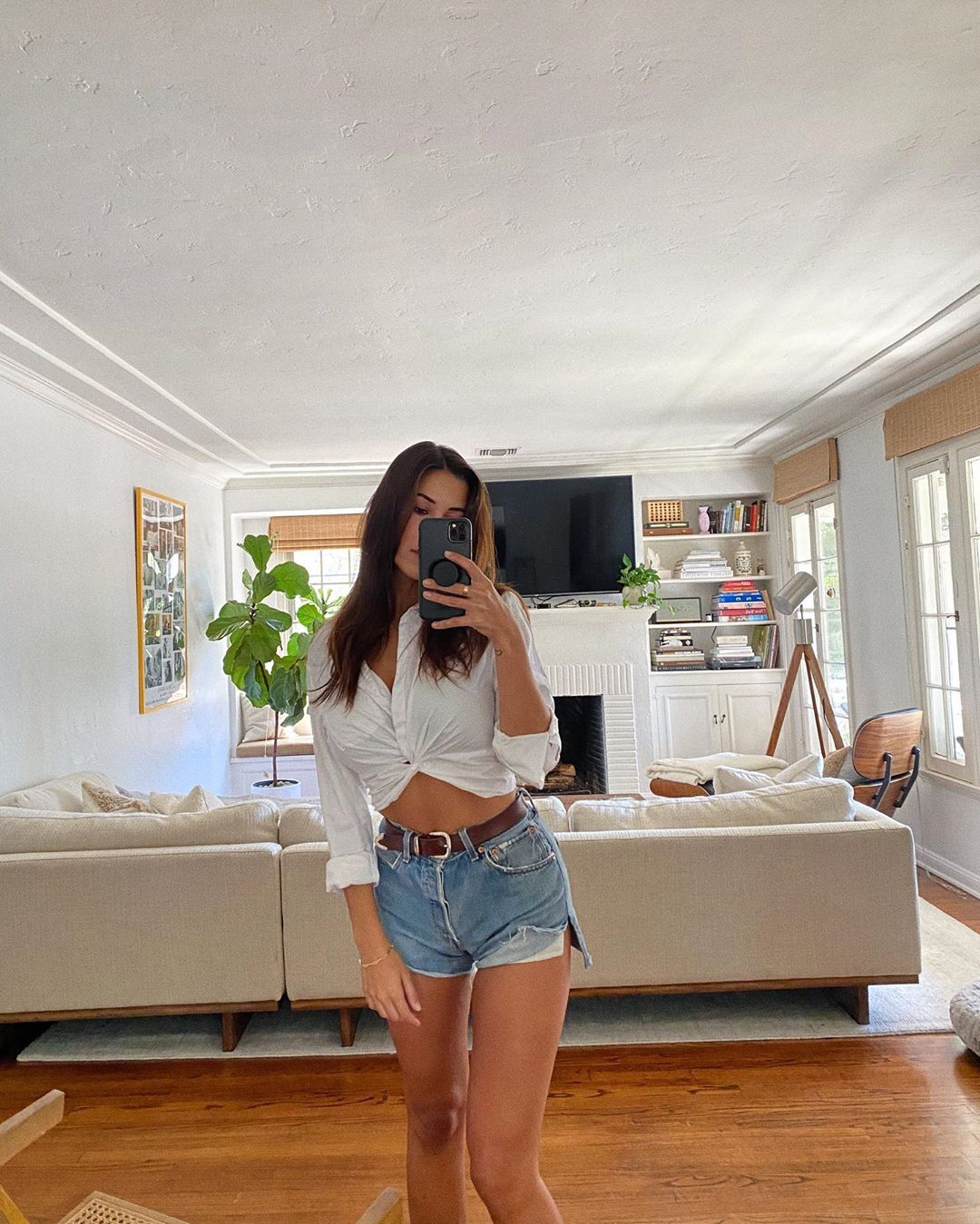Devin Brugman rocking a Close fitting white LAcademie crop top with 3/4 sleeves, asymmetric design and a scoop neck