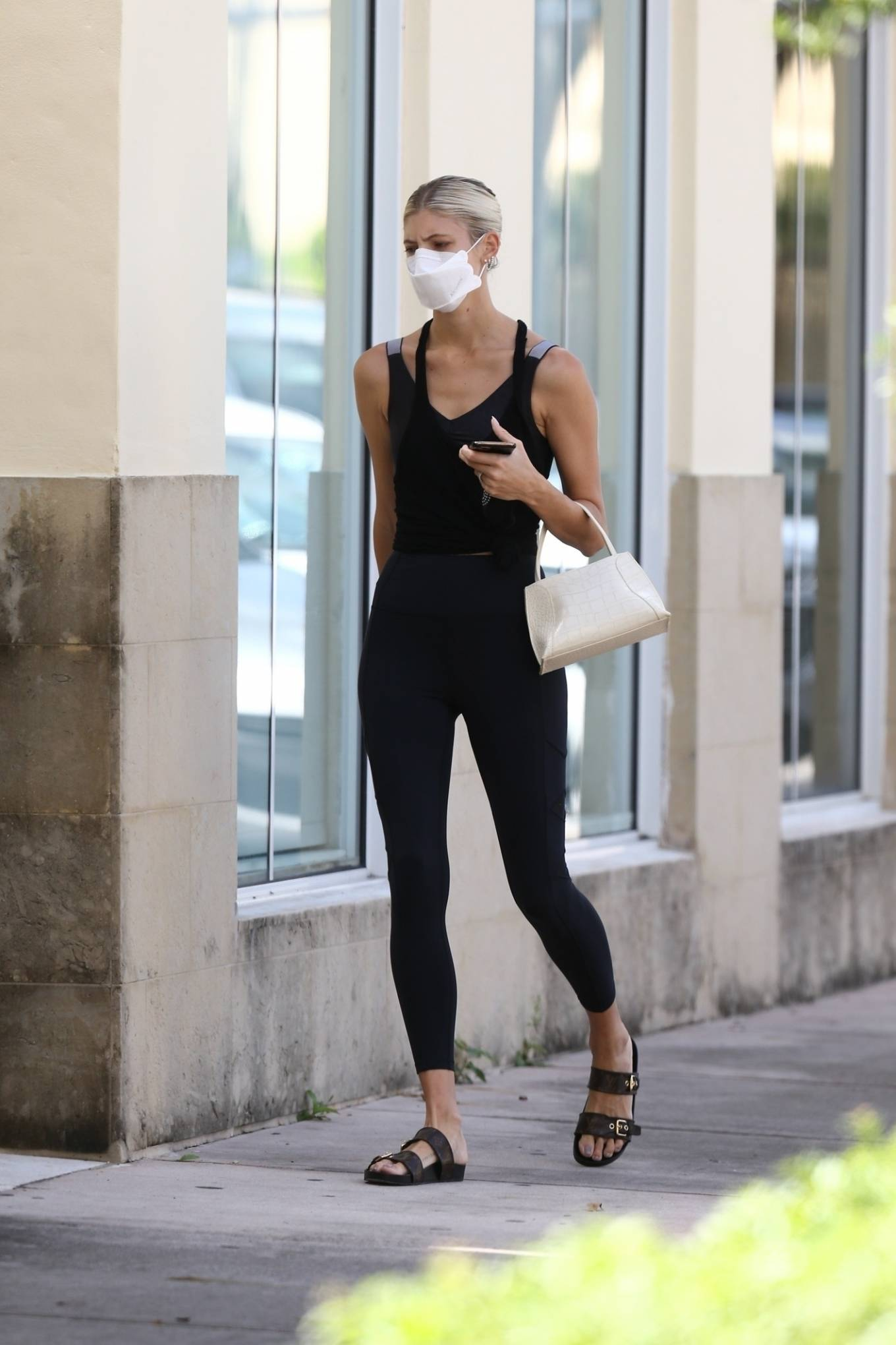 Devon Windsor wearing a figure hugging black tank top with knotted, a V-neck and wide strap