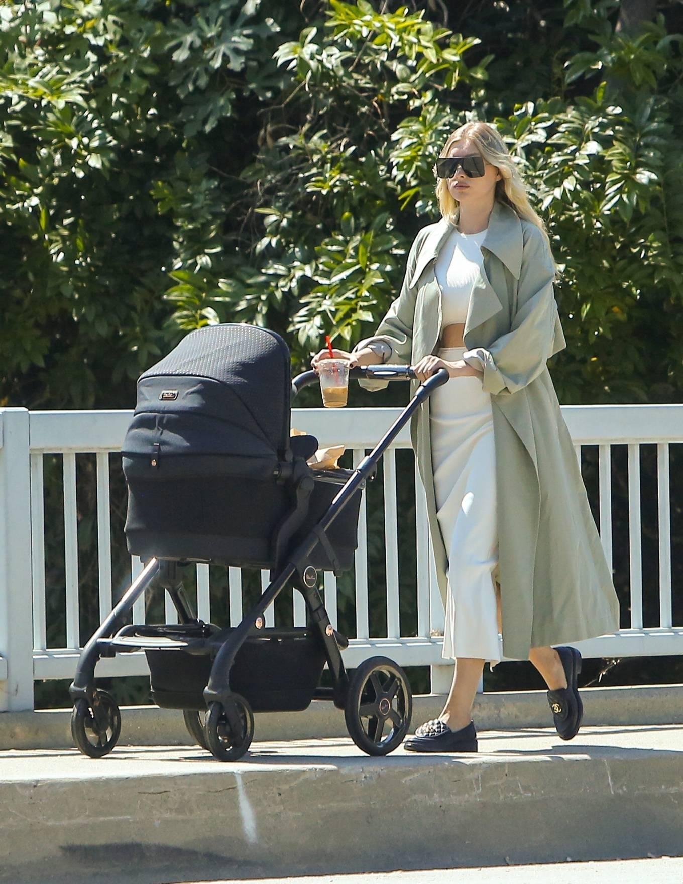 Elsa Hosk, black loafers, black sunglasses, white dress, round, white overcoat. Elsa Hosk donning round black loafers