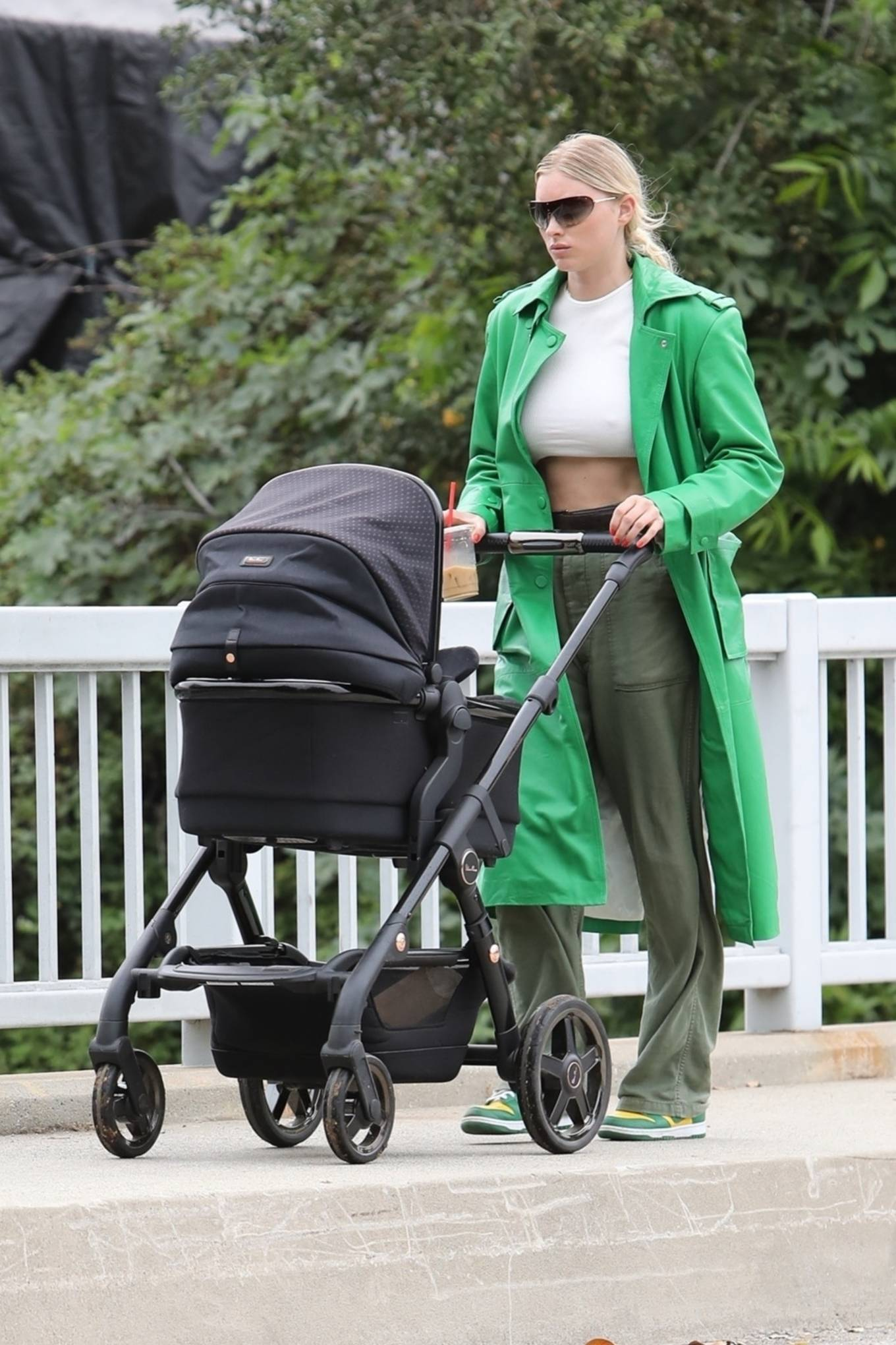 Elsa Hosk rocking brand logo yellow green lace-up sneakers by Nike with flat heel