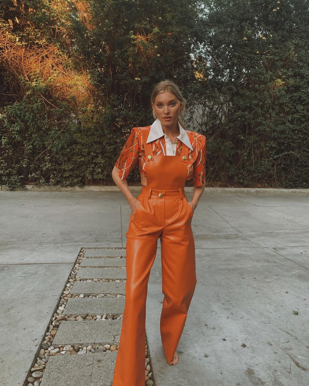 Elsa Hosk wearing a flare orange jumpsuit with a leather fabric, side pockets, a square neck and straps