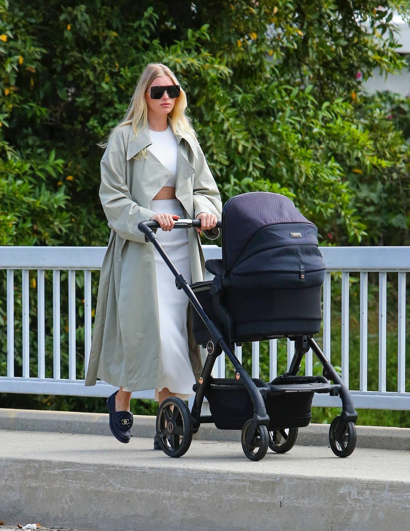 Elsa Hosk, black loafers, white dress, black sunglasses, round, white overcoat. Elsa Hosk donning round black loafers