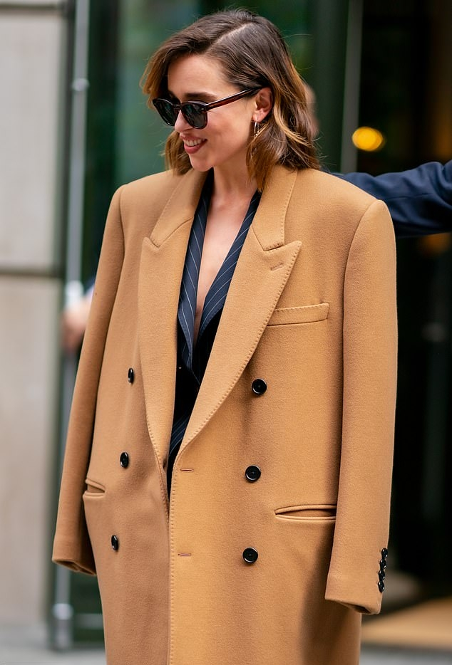 Emilia Clarke, Celine trench coat, camel trench coat. Emilia Clarke wearing a Oversized camel Celine cashmere double breasted trench coat with a cashmere material, full sleeves, peak lapel collar and button front
