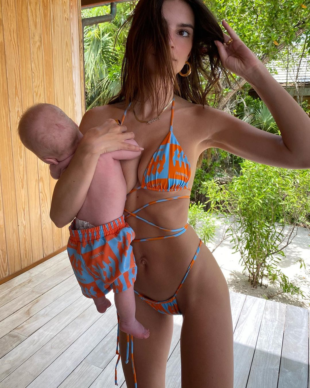 Emily Ratajkowski rocking a plunging bi color bikini top with tie back, a halter neck and two ties at the shoulder