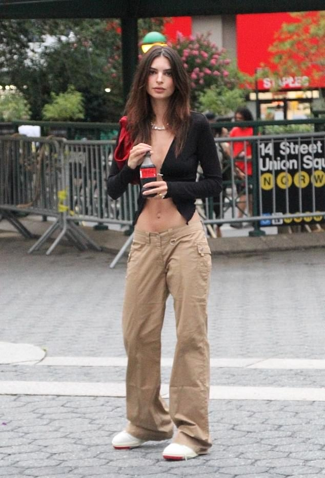 Emily Ratajkowski wearing round white cream lace-up sneakers by New Balance with flat heel