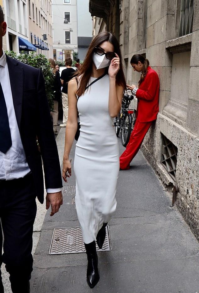 Emily Ratajkowski wearing a figure hugging white dress with a gathered round neck
