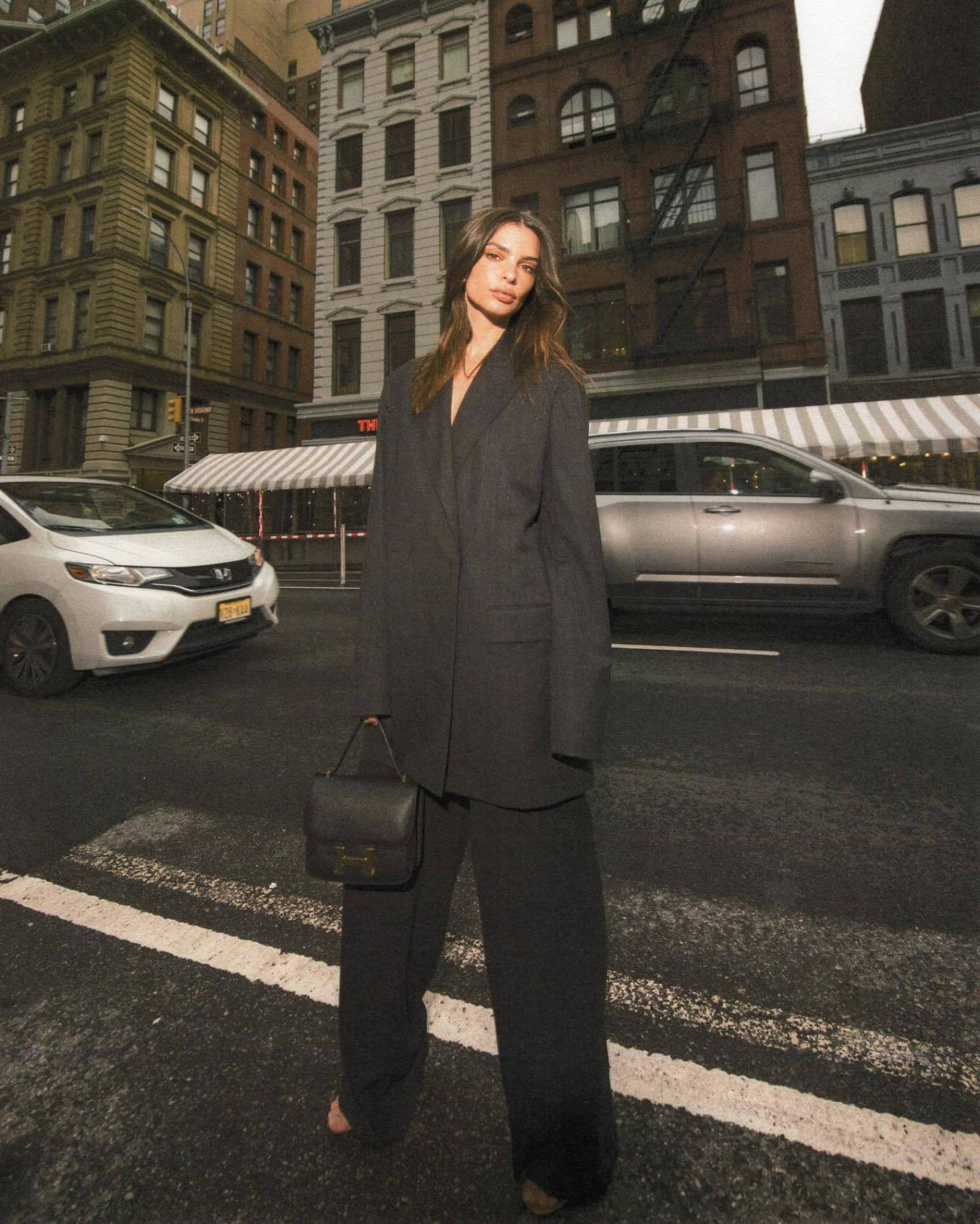 Emily Ratajkowski rocking a oversized black coat with full sleeves and lapel collar