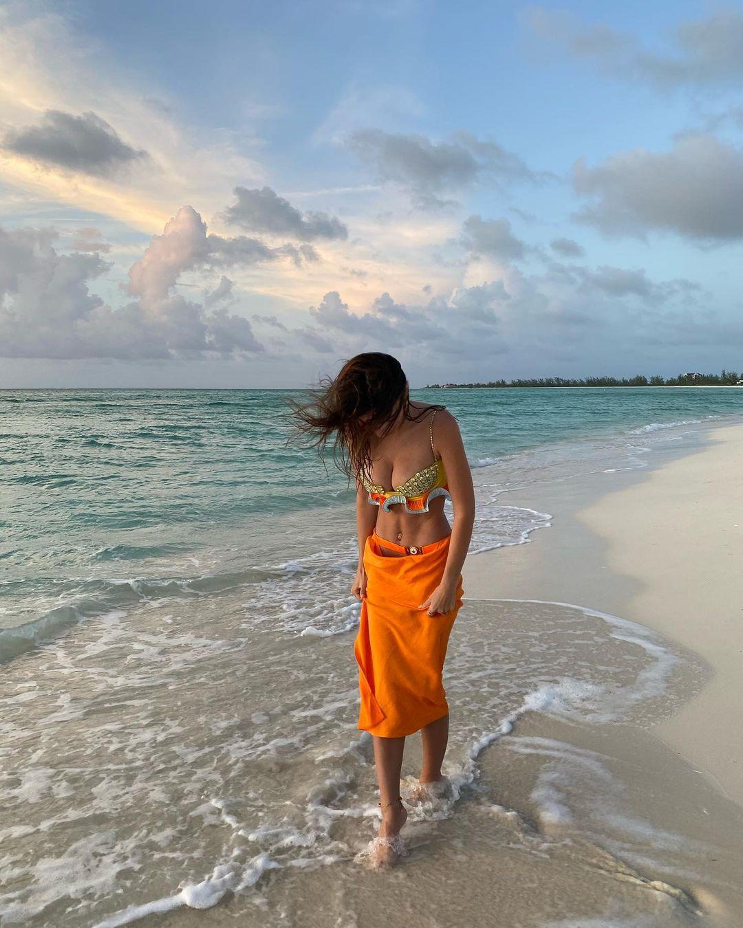 Emily Ratajkowski wearing a orange fitted skirt
