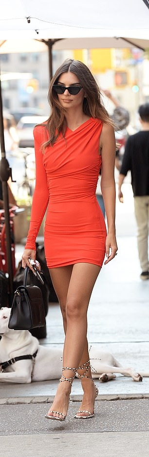 Emily Ratajkowski wearing a figure hugging red dress with full sleeves and a V-neck