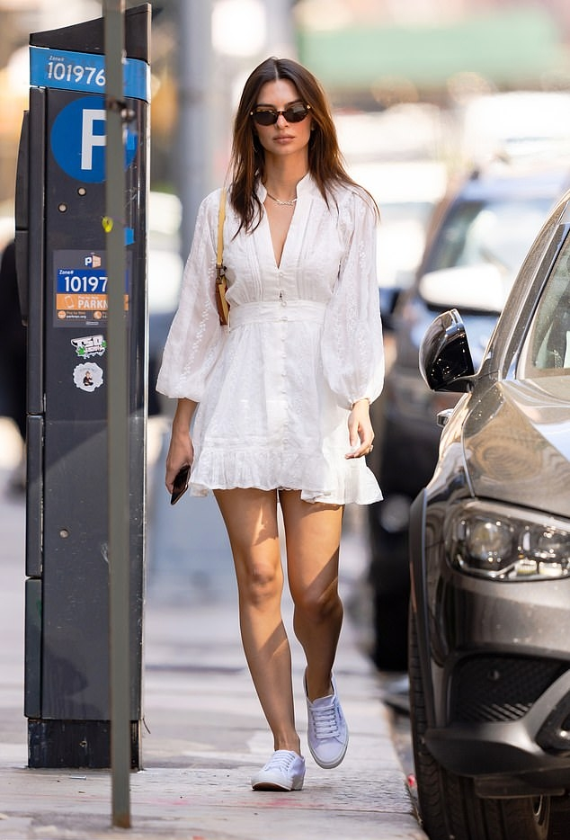 Emily Ratajkowski rocking a plunging white dress with bell sleeves and ruffled