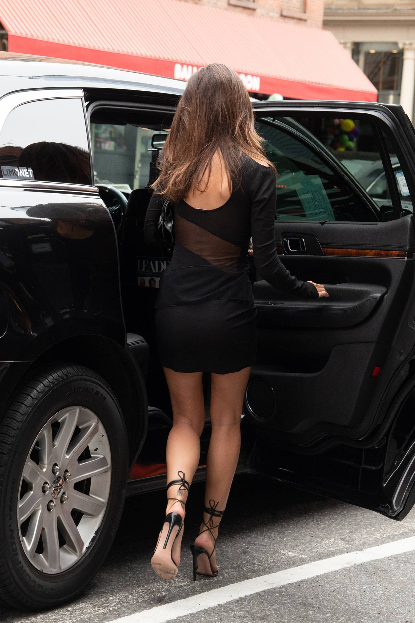 Emily Ratajkowski donning pointed black crisscross tie sandals with high heel