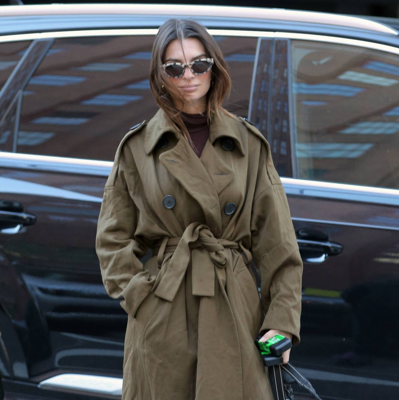 Emily Ratajkowski, white  sneakers, oversized olive green trench coat, black sunglasses, round, lace-up, flat heel, grey trousers, brand logo