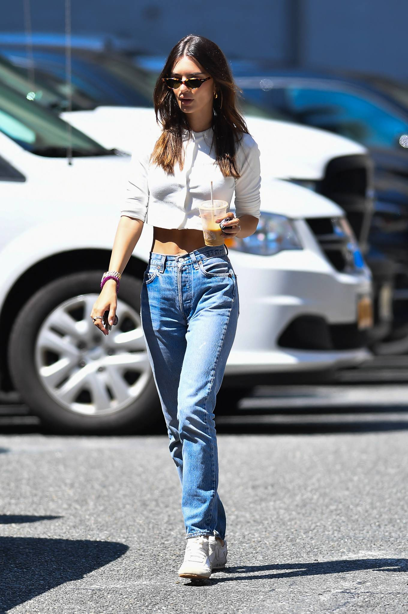 Emily Ratajkowski donning brand logo white off white lace-up sneakers by Loewe with flat heel