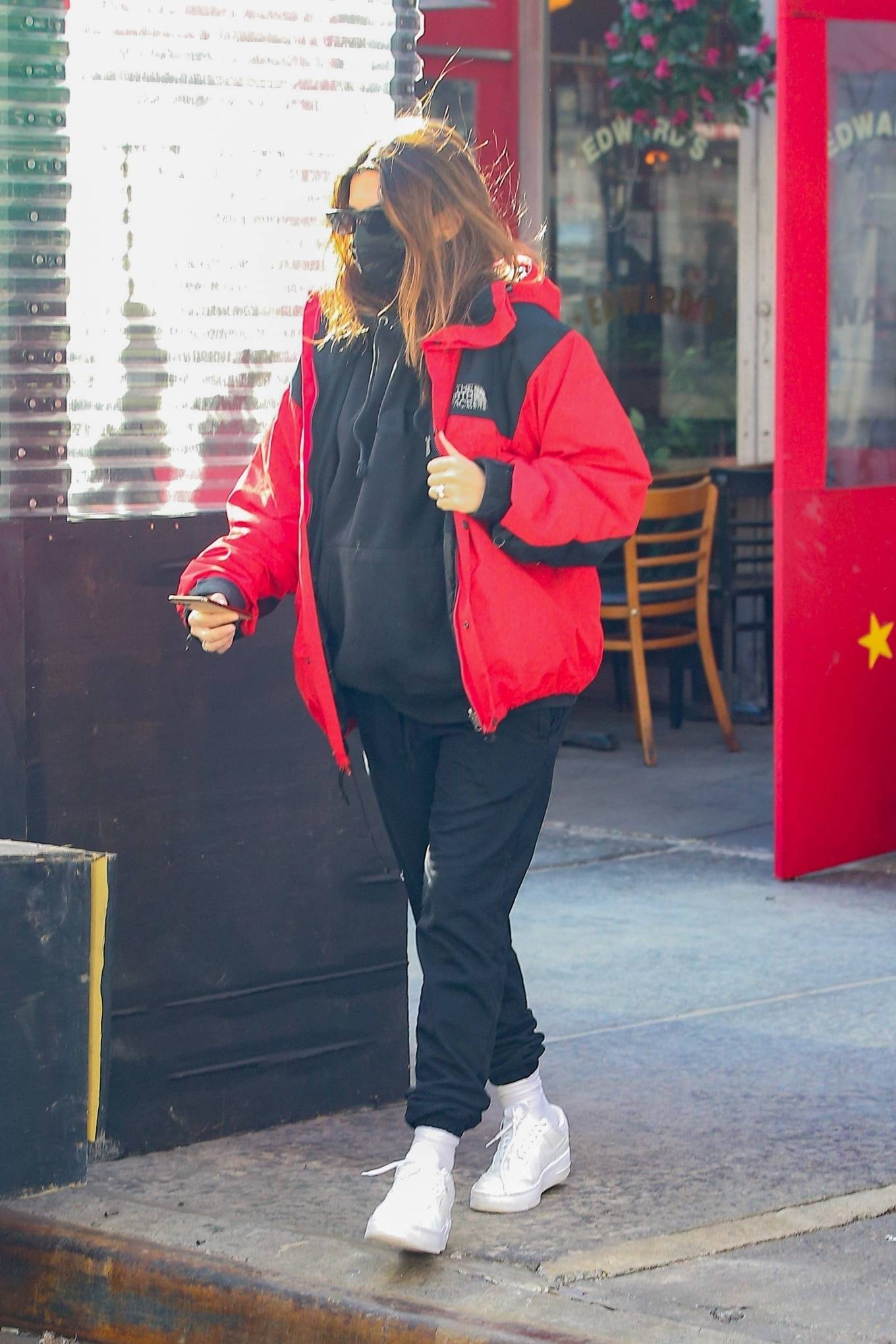 Emily Ratajkowski donning a relaxed fit black and red hooded nylon jacket with a polyester material, full sleeves and button front