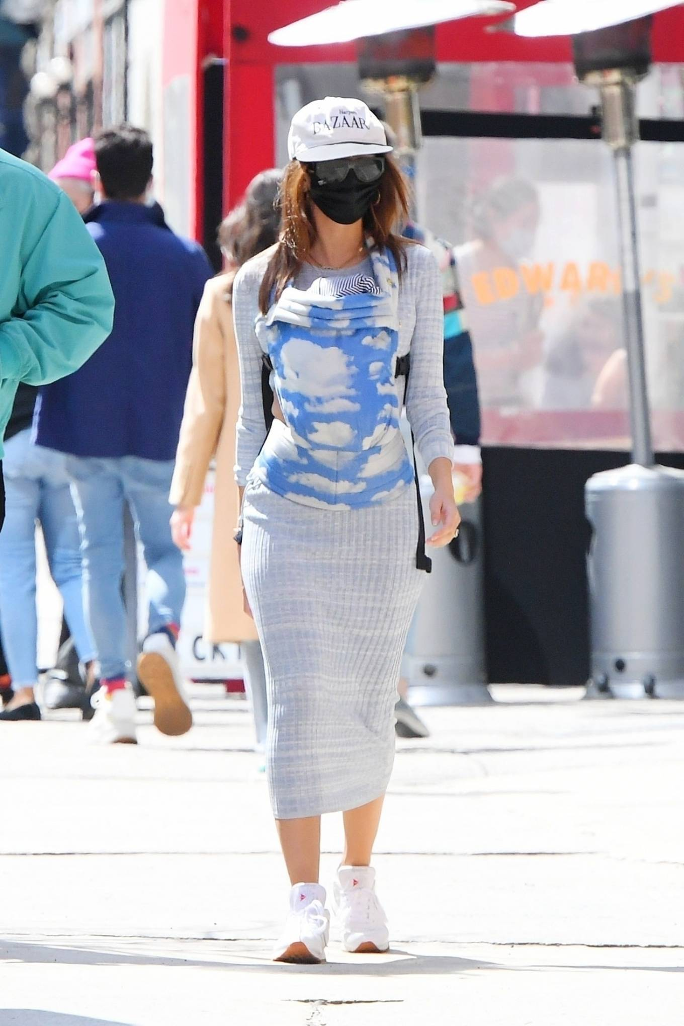 Emily Ratajkowski wearing a figure hugging grey dress with a viscose material, full sleeves, cut out and a round neck