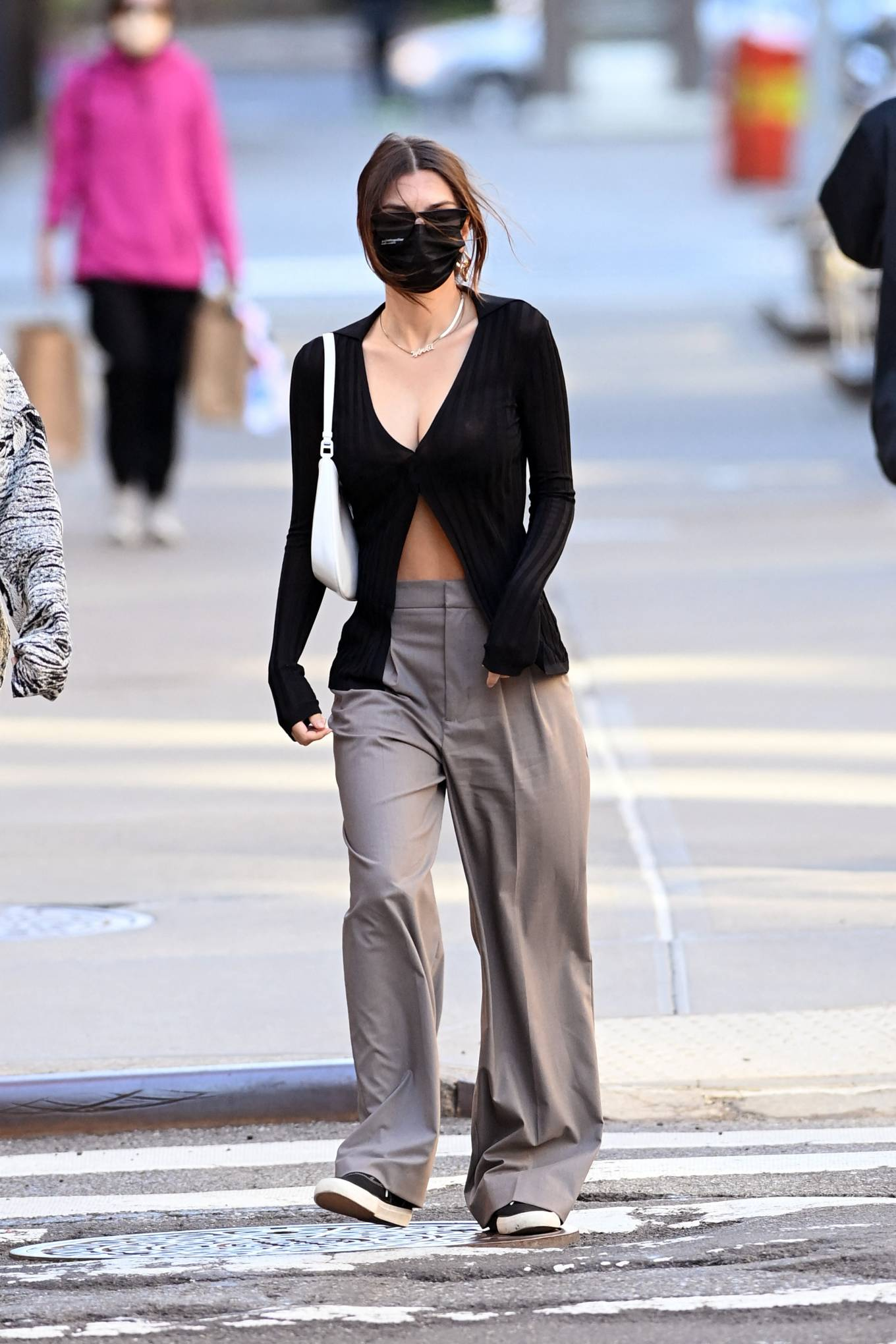 Emily Ratajkowski, Keds sneakers, black sneakers, white Prada shoulder bag, black Aya Muse cardigan, round, lace-up, flat heel, canvas, black sunglasses, grey trousers. Emily Ratajkowski rocking round black canvas lace-up sneakers by Keds with flat heel