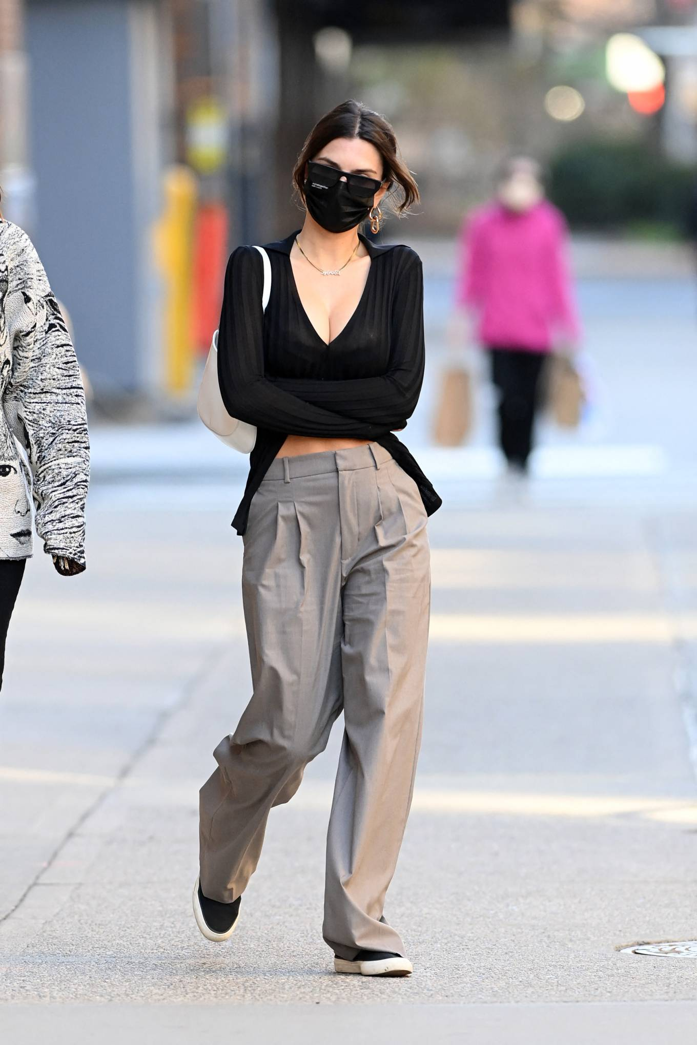 Emily Ratajkowski, black sneakers, Keds sneakers, white Prada shoulder bag, black Aya Muse cardigan, flat heel, canvas, round, lace-up, black sunglasses, grey trousers. Emily Ratajkowski rocking round black canvas lace-up sneakers by Keds with flat heel
