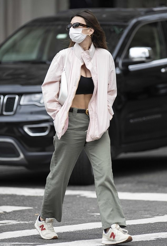 Emily Ratajkowski donning brand logo white lace-up sneakers by New Balance with flat heel