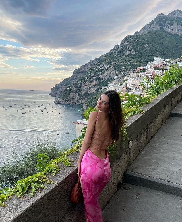 Emily Ratajkowski donning a figure hugging bright pink dress with a silk fabric, floral print and spaghetti straps