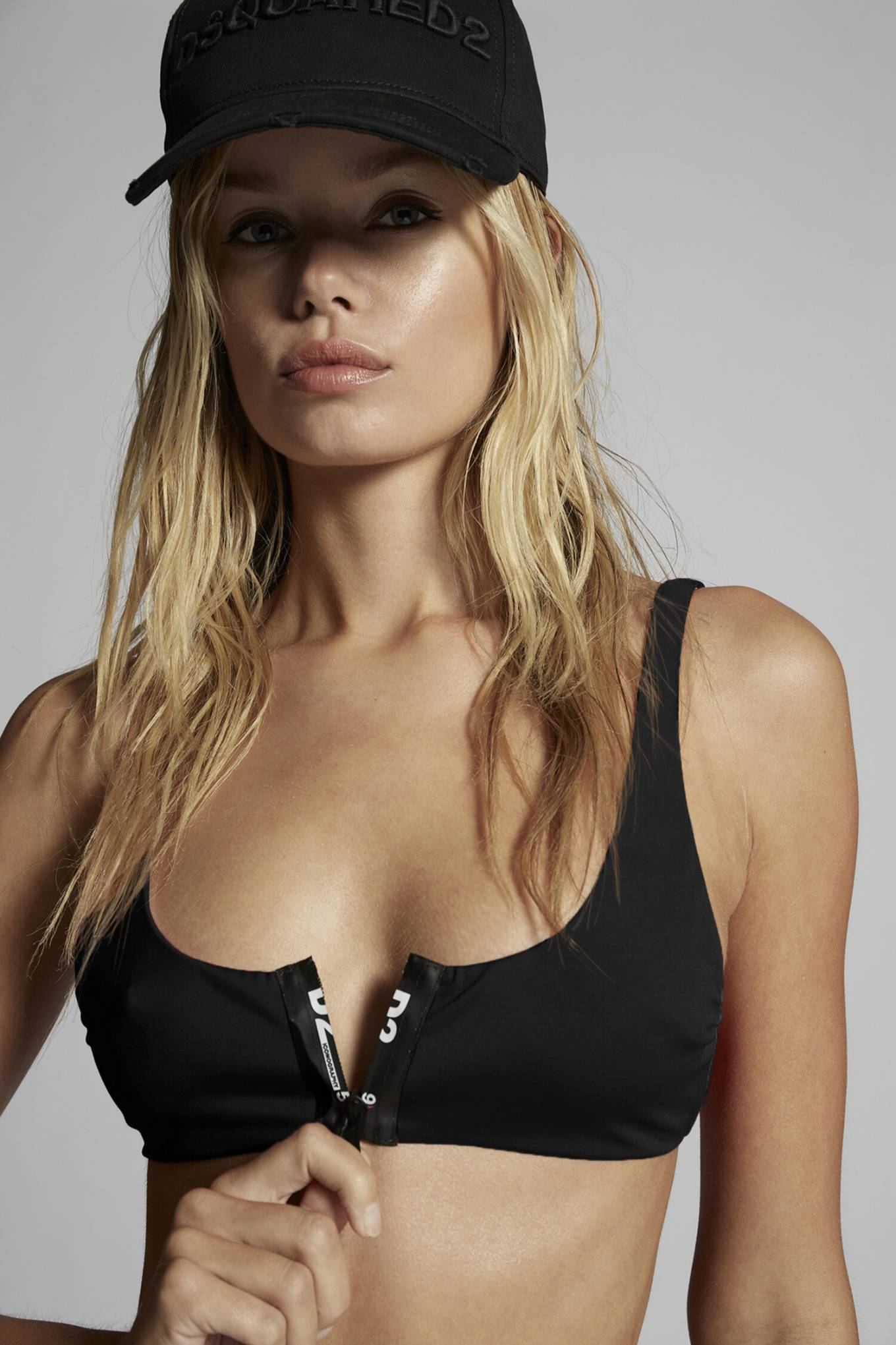 Frida Aasen donning a skimpy black bikini top with brand logo, a scoop neck and straps