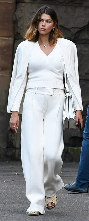Georgia Fowler wearing brand logo beige slip on sandals