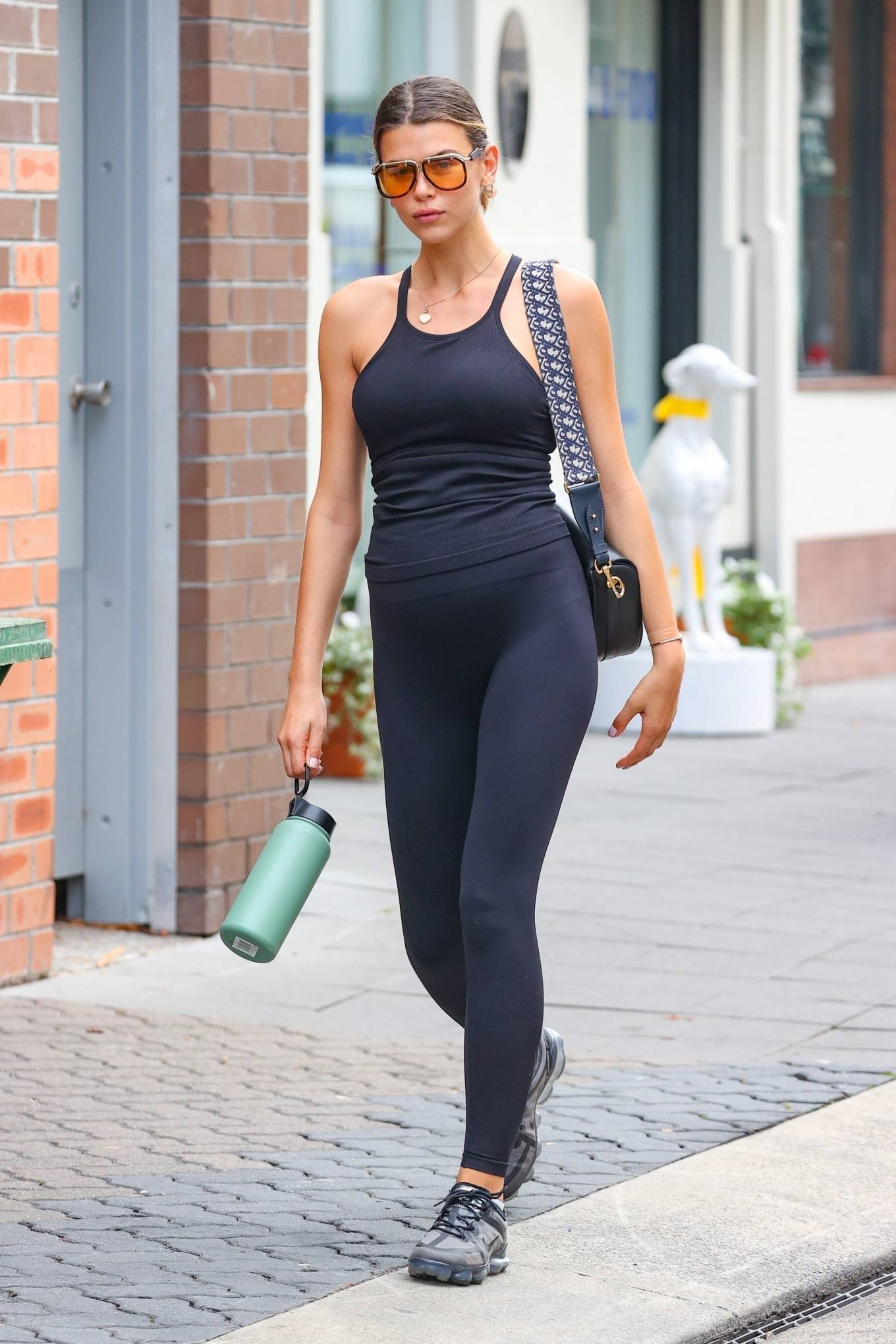 Georgia Fowler donning a figure hugging black camisole with a round neck and straps