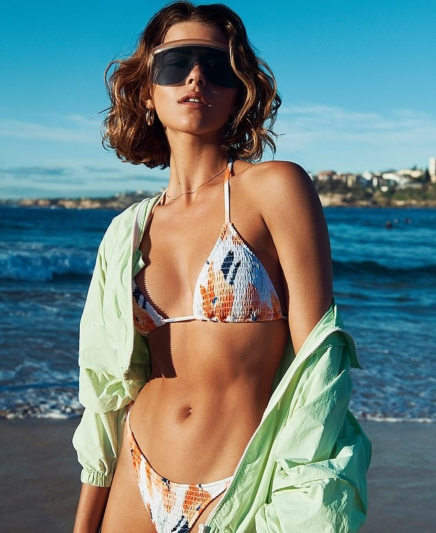 Georgia Fowler, white bikini top, nylon, black sunglasses, mint green jacket, floral, sexy, tie back, skimpy, flaunt, beaded, plunging, flat stomach, taut midriff. Georgia Fowler donning a plunging white bikini top with a nylon fabric, tie back and Shirred Detailing