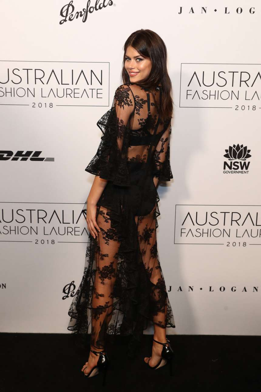 Georgia Fowler wearing a sheer black dress with a lace detailing material, ruffle sleeves, asymmetric design, a crew neck and flared hem
