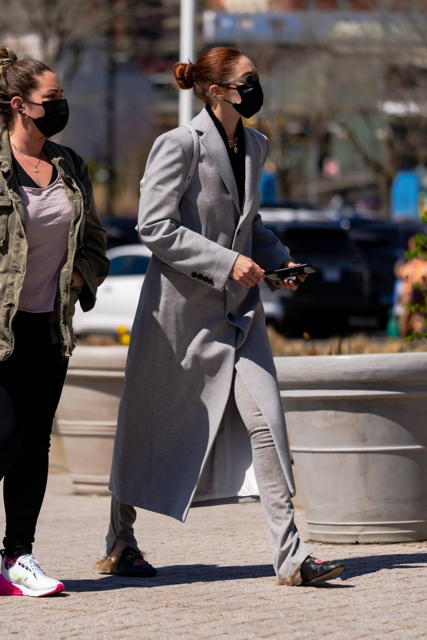 Gigi Hadid wearing metal detailing black Gucci slip on mules with flat heel