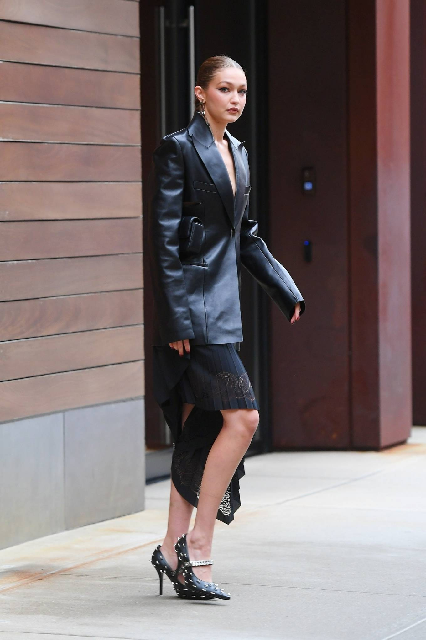 Gigi Hadid donning chain detailing black Givenchy slip on pumps with stiletto heels and Studded rings all over