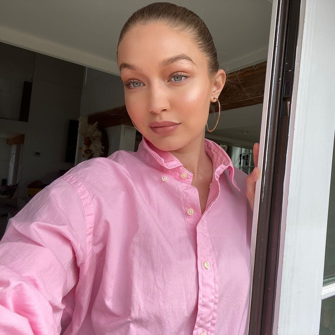 Gigi Hadid wearing a Oversized pink US Polo shirt with a jersey fabric, elbow length sleeves, shirt collar and button front