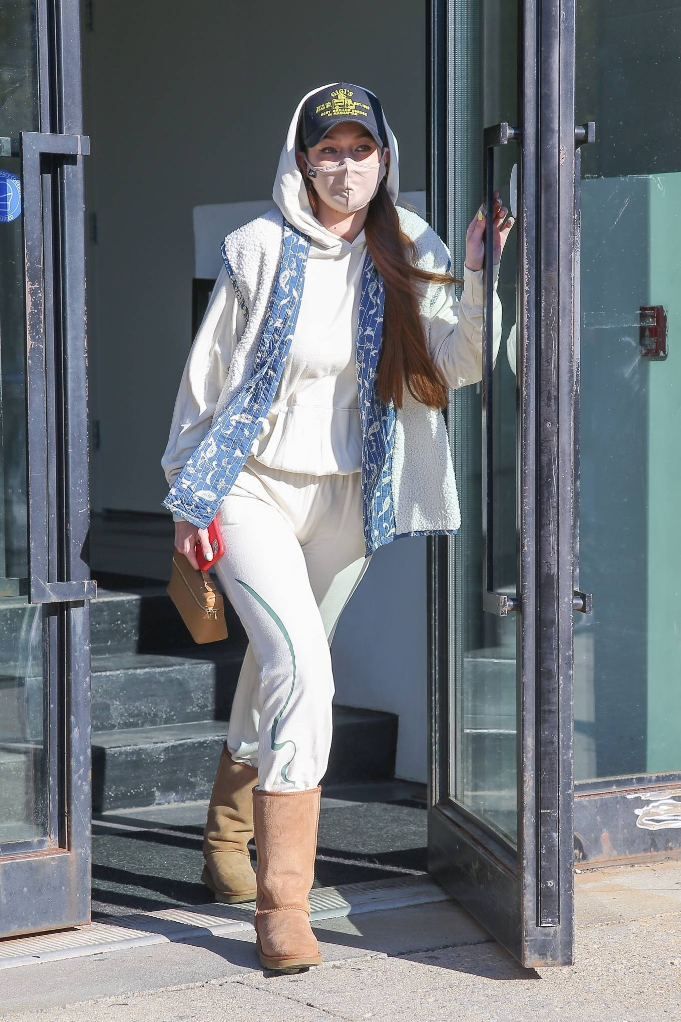 Gigi Hadid donning round chestnut brown Ugg knee high boots with flat heel