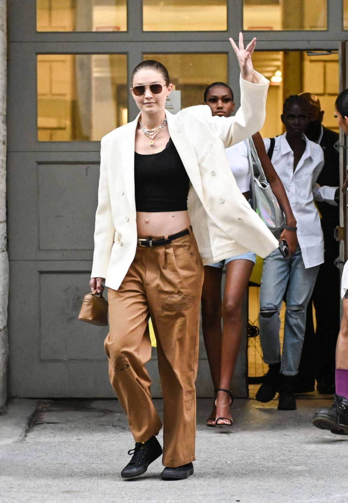 Gigi Hadid donning brand logo black Converse lace-up canvas shoes with flat heel