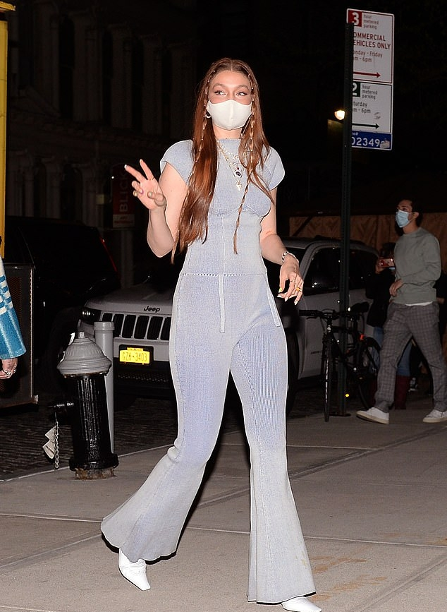 Gigi Hadid rocking a fitted light blue blouse with a nylon material, short sleeves, tie back and a round neck