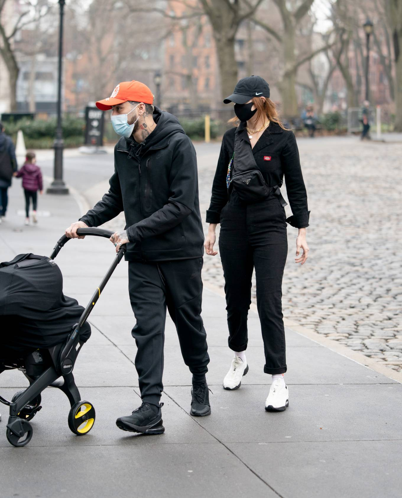Gigi Hadid, black  jumpsuit, cotton, Dickies  jumpsuit, white Reebok sneakers, full length, long sleeved, lapel collar, fitted, patch pocket, black Prada fanny pack, straight fit, brand logo, button front