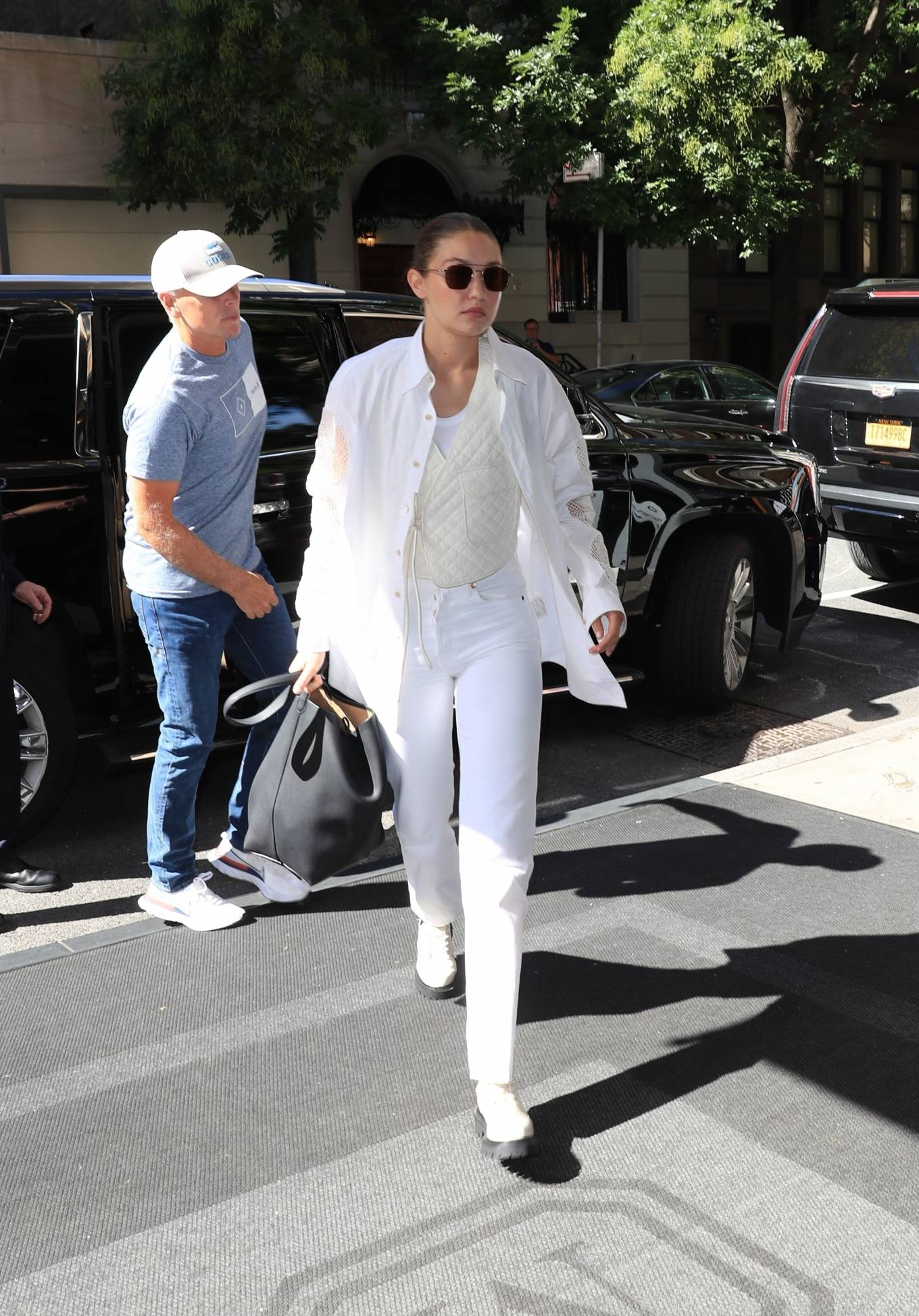 Gigi Hadid wearing a oversized white cotton shirt with full sleeves, shirt collar and embroidered cutout detailing on the sleeve