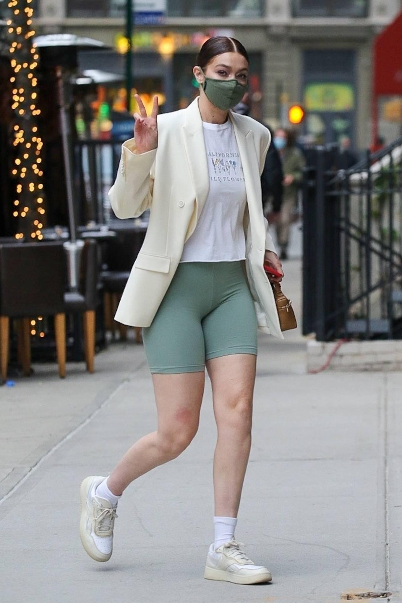 Gigi Hadid rocking round off white Reebok lace-up sneakers with flat heel