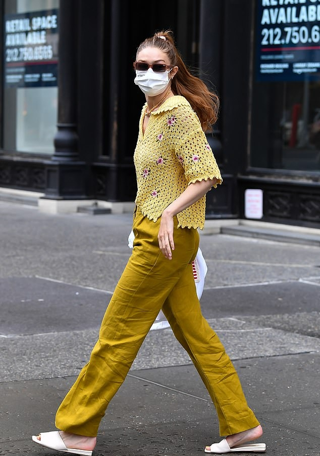 Gigi Hadid wearing a relaxed fit yellow top with a knit fabric, half sleeves, spread collar, floral print and a V-neck