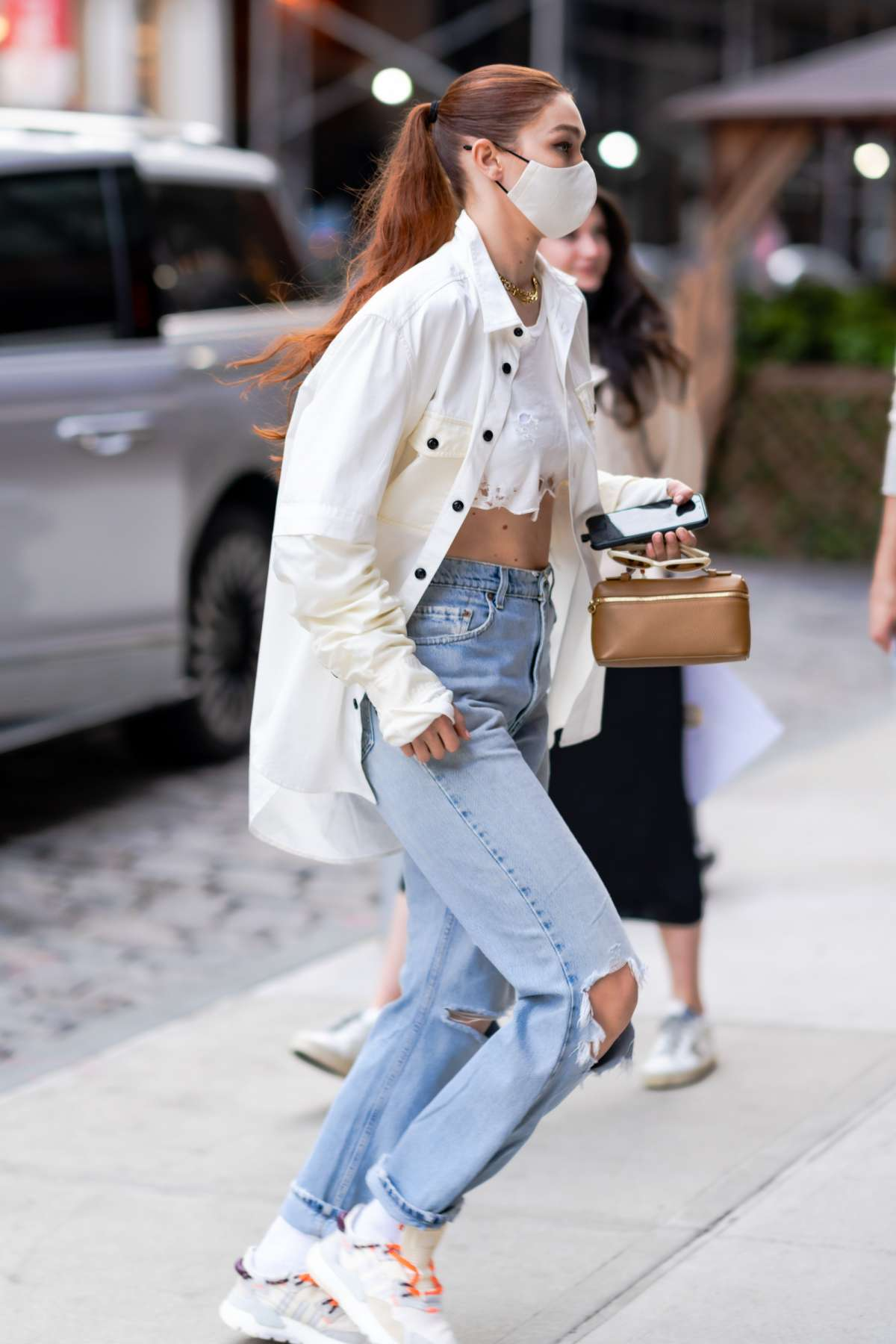 Gigi Hadid rocking round white orange lace-up sneakers by Adidas with flat heel