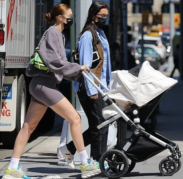 Gigi Hadid donning floral multicolor Versace lace-up sneakers with chunky sole