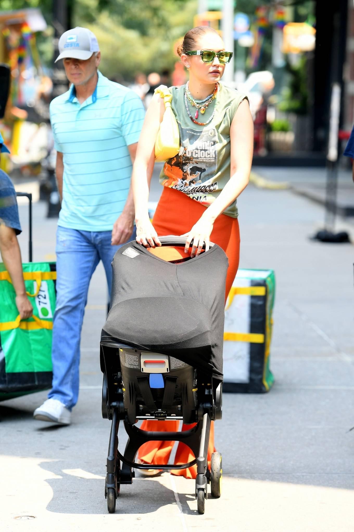 Gigi Hadid rocking orange flared hem trousers with woven