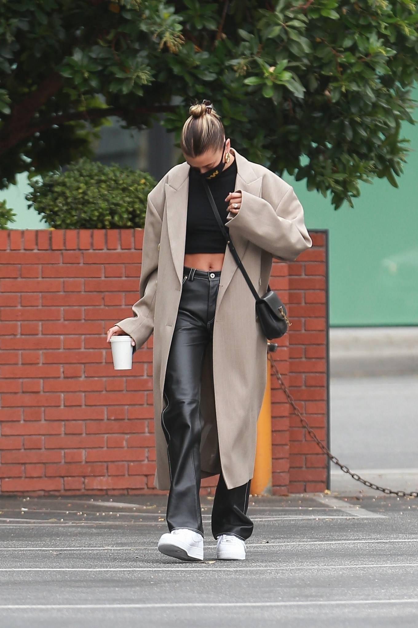 Hailey Bieber wearing Straight fit black leather Loewe high rise jeans with a leather material
