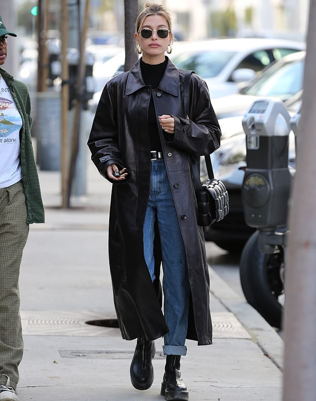 Hailey Bieber donning a oversized black button front leather trench coat with extra long sleeves, wide collar and flap pockets