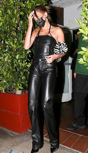 Hailey Bieber wearing straight fit black leather high waist trousers